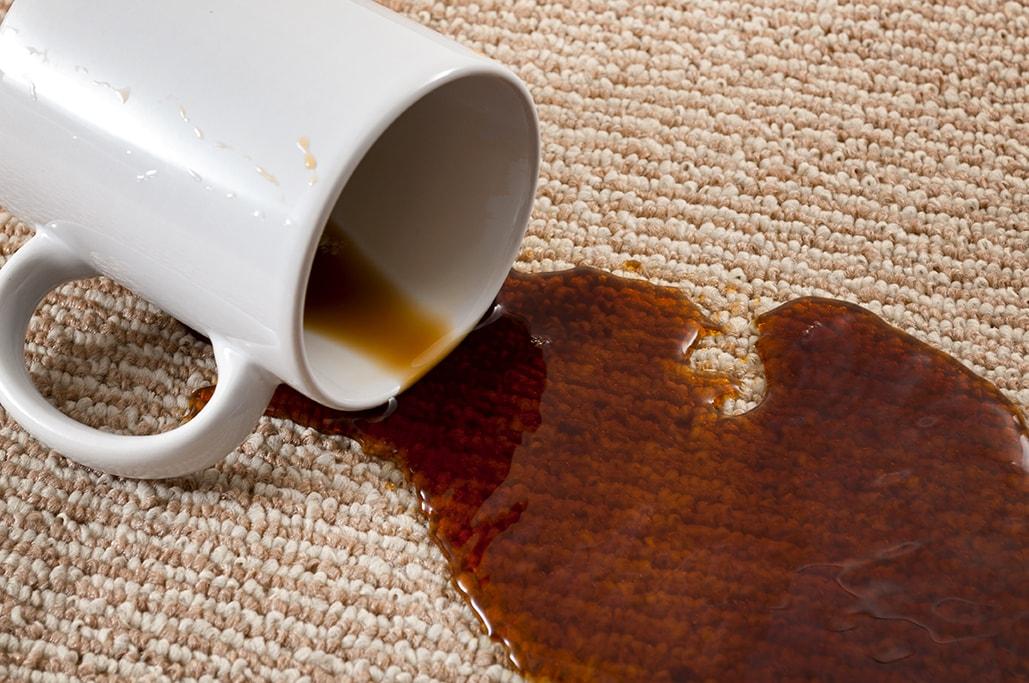 Tasse de café renversée sur un tapis avec une grosse tache de café